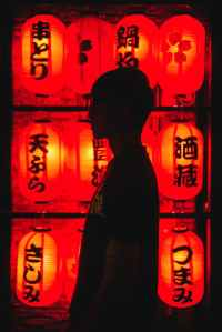 man standing beside red chinese lanterns