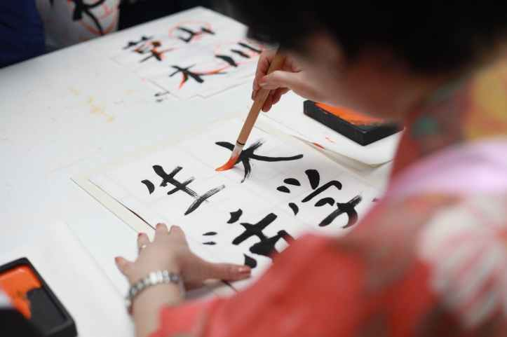 person holding brush drawing kanji script